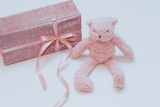 prezent dla dziewczynki w różowym, brokatowym papierze, z różową wstążką, różowy miś na dzień dziecka