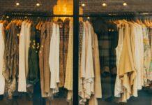 brązowe, beżowe i kremowe swetry na wieszaku w sklepie