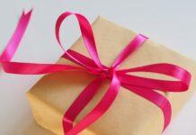 mały prezent w brązowym papierze owinięty różową wstążką
