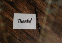 biała kartka z napisem thanks na drewnianym stole