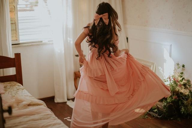 kobieta w różowej sukience i kokardce we włosach, suknia wieczorowa