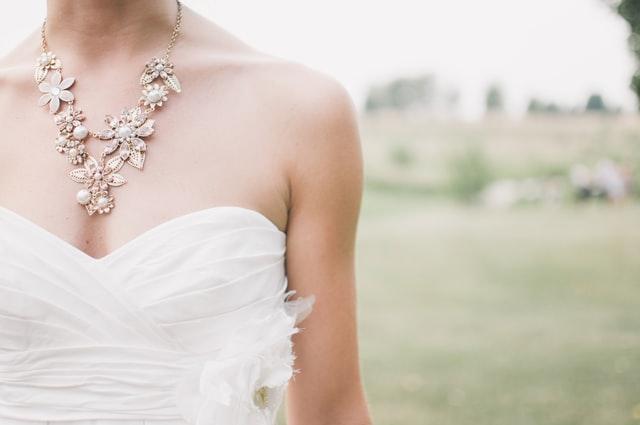 panna młoda w sukni ślubnej i naszyjniku z kamieniami szlachetnymi