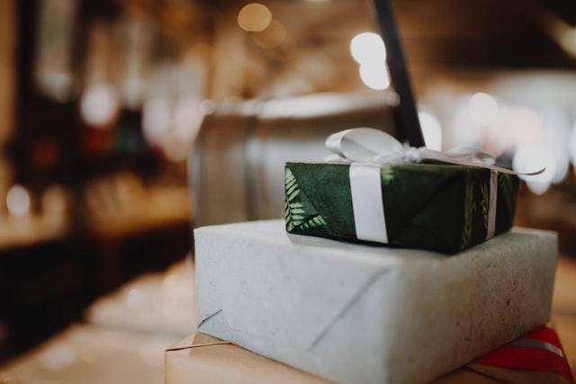prezent w zielonym papierze z białą wstążką, prezent w szarym papierze