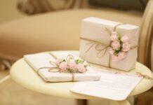 dwa prezenty zapakowane w jasny papier, przewiązane brązową wstążką i ozdobione różowymi kwiatami