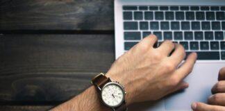 mężczyzna pisze na laptopie, MacBook, męski zegarek na skórzanej bransolecie
