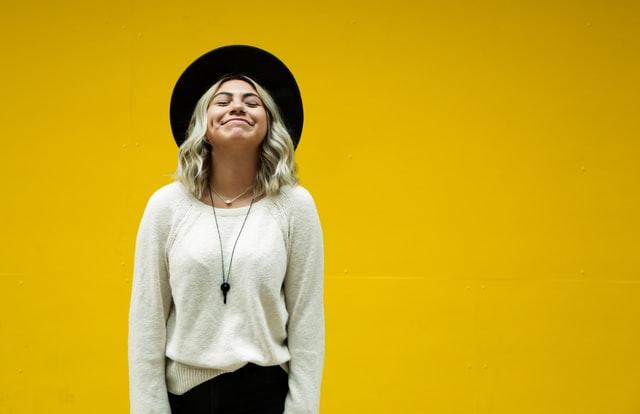 blondynka na żółtym tle, jasny sweter, czarny kapelusz, stylizacja